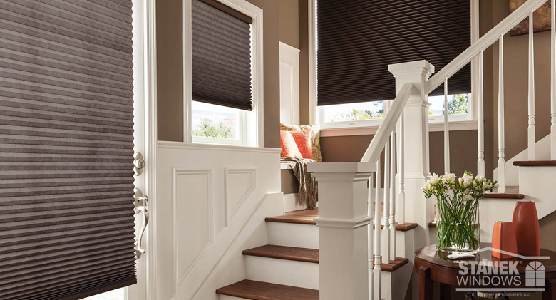 Dark brown window shades on windows up a staircase
